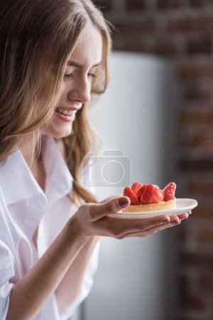 Photo for Smiling young woman holding tasty strawberry cake on plate - Royalty Free Image