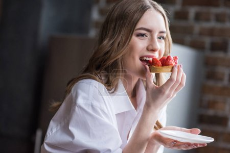 Photo for Smiling young woman in white shirt eating strawberry cake - Royalty Free Image