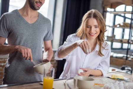 Photo for Young couple cooking together with eggs and flour in kitchen - Royalty Free Image