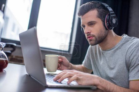 Photo for Young concentrated man in headphones using laptop and drinking coffee - Royalty Free Image