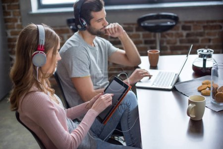 Photo for Young couple in headphones using laptop and digital tablet - Royalty Free Image