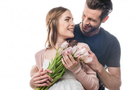 Photo pour Jeune homme hugging femme enceinte qui tenant le bouquet de tulipes fraîches - image libre de droit
