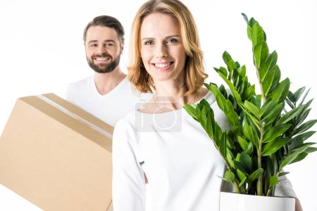 Photo for Young smiling couple holding cardboard box and green plant isolated on white - Royalty Free Image