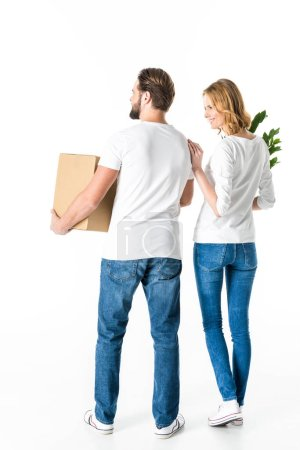 Photo for Back view of young couple holding cardboard box and green plant isolated on white - Royalty Free Image