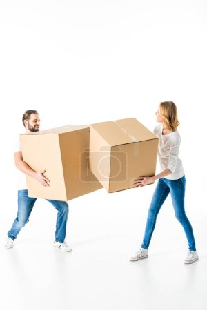 Photo for Smiling young couple having fun with cardboard boxes  isolated on white - Royalty Free Image