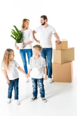 Photo for Happy family with cardboard boxes and green plant moving into new house  isolated on white - Royalty Free Image