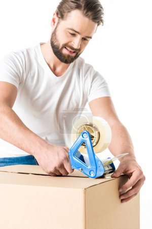 Photo for Young bearded man packing cardboard box  isolated on white - Royalty Free Image