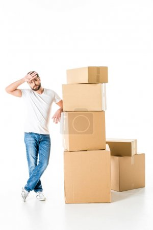 Photo for Young tired man leaning on stack of cardboard boxes isolated on white - Royalty Free Image