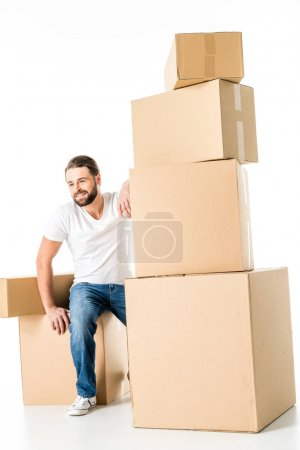 Photo for Young bearded smiling man sitting with cardboard boxes  isolated on white - Royalty Free Image