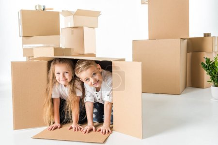 Photo for Cute little kids having fun in cardboard box and smiling at camera isolated on white - Royalty Free Image