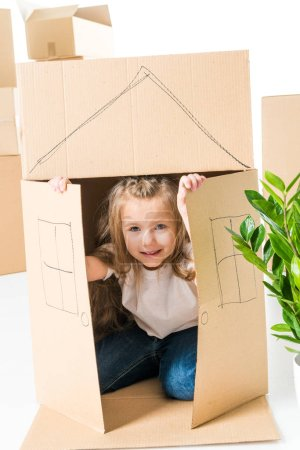 Foto de Cute little girl sittling inside of cardboard box with house drawed on it isolated on white - Imagen libre de derechos