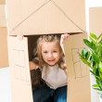 Cute little girl sittling inside of cardboard box ...