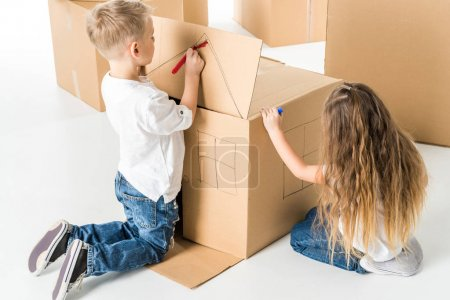 Photo for Cute little boy and girl drawing house on cardboard box isolated on white - Royalty Free Image