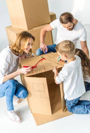 Photo pour Joyeux jeune famille de quatre dessin sur boîte en carton ensemble isolé sur blanc - image libre de droit
