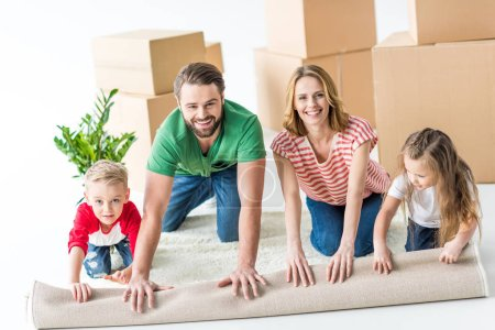 Photo for Happy young family of four unrolling carpet after moving into new house isolated on white - Royalty Free Image