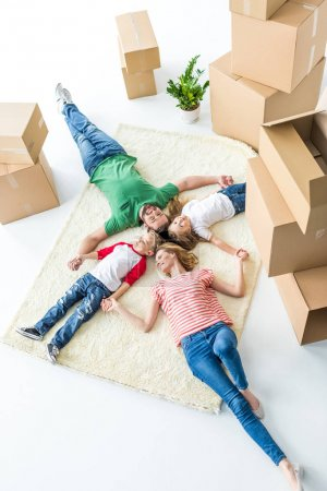 Photo for Top view of young family of four relaxing on carpet after moving into new house isolated on white - Royalty Free Image