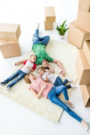 Photo for Top view of happy young family relaxing on carpet after moving into new house isolated on white - Royalty Free Image