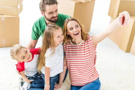 Photo for Happy young family of four making selfie on smartphone among cardboard boxes  isolated on white - Royalty Free Image