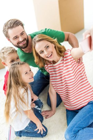Photo for Happy young family of four making selfie on smartphone isolated on white - Royalty Free Image