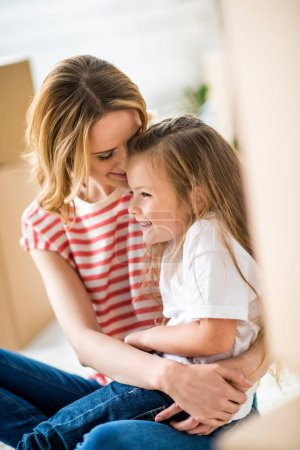 Photo for Young beautiful woman embracing cute little girl and smiling - Royalty Free Image