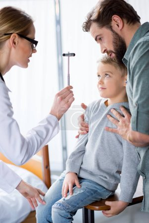 Doctor inspecting little boy
