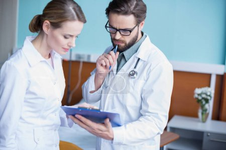 Photo for Concentrated young male and female doctors looking in clipboard - Royalty Free Image