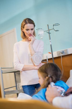 Photo for Young concerned woman watching doctor examining her daughter in hospital - Royalty Free Image