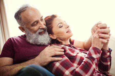 Photo pour Heureux mature couple assis ensemble et tenant la main à la maison - image libre de droit
