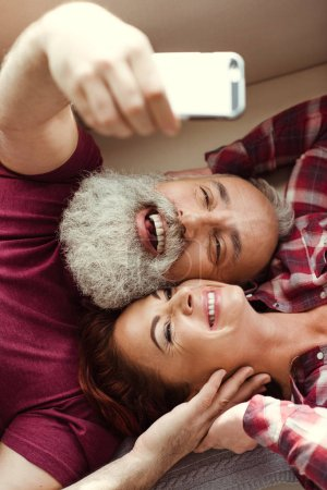 Photo for Top view of happy mature couple lying together and taking selfie - Royalty Free Image