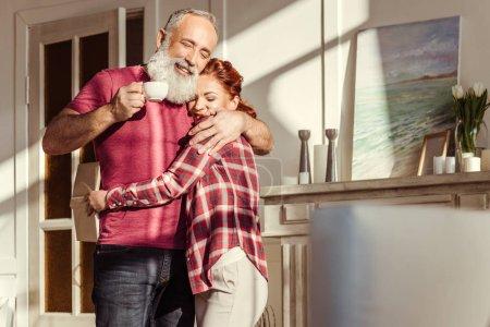 Photo pour Heureux mature homme tenant tasse de café et étreignant belle femme avec livre - image libre de droit