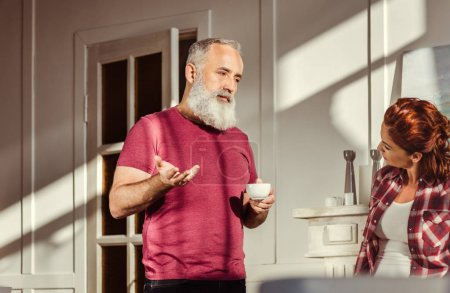 Photo for Bearded mature man holding coffee cup and talking with redhead woman - Royalty Free Image