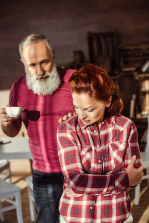 Photo for Mature bearded man with coffee cup talking to dissatisfied woman - Royalty Free Image