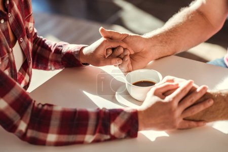 Photo for Close-up partial view of couple holding hands at table with coffee cup - Royalty Free Image