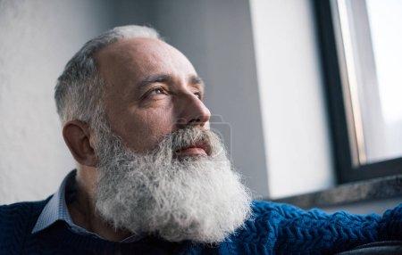 Photo pour Vue rapprochée d'un cher homme âgé barbu regardant à distance - image libre de droit