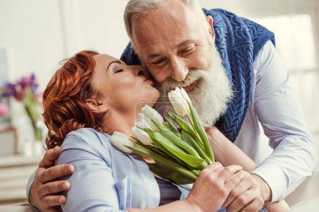Photo pour Femme mature embrassant homme barbu alors qu'il lui donne un bouquet de fleurs de tulipes - image libre de droit