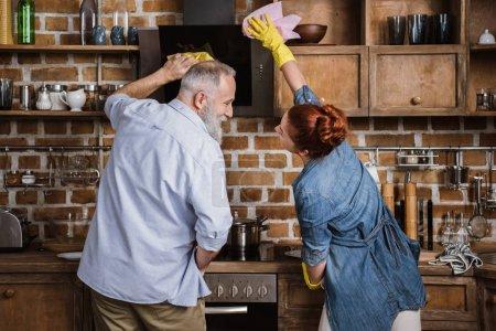 Photo pour Vue arrière du couple senior s'amuser pendant le nettoyage des appareils de cuisine - image libre de droit