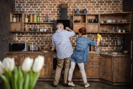 Photo pour Vue arrière du couple senior s'amuser tout en lavant la vaisselle dans la cuisine - image libre de droit