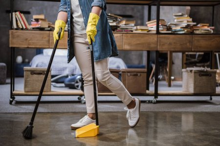 Photo for Partial view of woman in gloves sweeping floor with broom and dustpan - Royalty Free Image