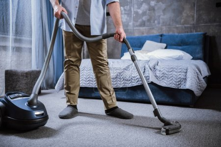 Photo for Partial view of man with vacuum cleaner cleaning carpet in bedroom - Royalty Free Image