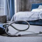 Vacuum cleaner on grey carpet in bedroom...