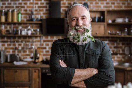 Старший мужчина с зеленью в бороде