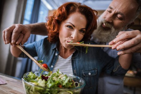 Photo for Happy mature couple cooking and tasting vegetable salad - Royalty Free Image