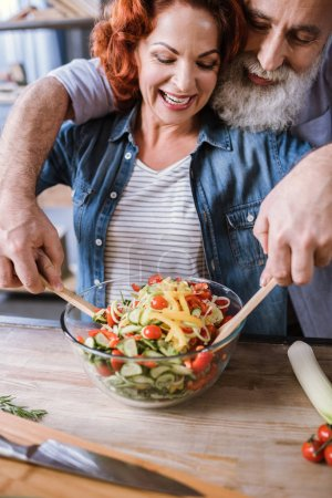 Photo for Happy mature couple mixing vegetable salad in bowl - Royalty Free Image