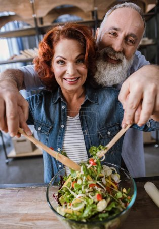 Photo for Happy mature couple cooking vegetable salad and smiling at camera - Royalty Free Image