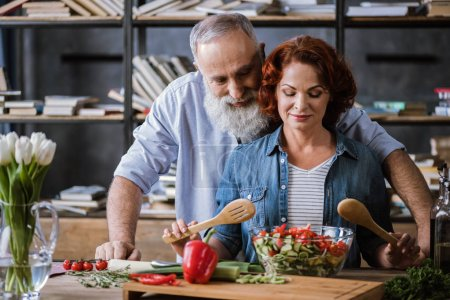 Photo for Smiling mature couple cooking healthy vegetable salad together - Royalty Free Image