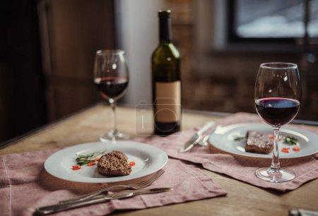 Photo for Red wine in glasses with wine bottle and delicious steaks on plates - Royalty Free Image