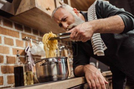 Photo pour Barbu senior cuisson spaghetti dans cuisine - image libre de droit