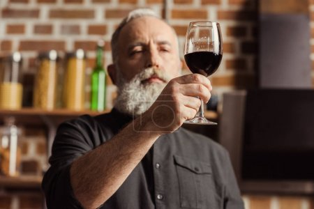 Photo for Bearded senior man looking at wine glass with red wine - Royalty Free Image