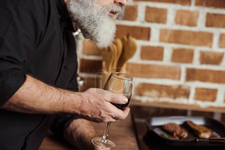 Photo for Partial view of bearded senior man holding wine glass with red wine in kitchen - Royalty Free Image
