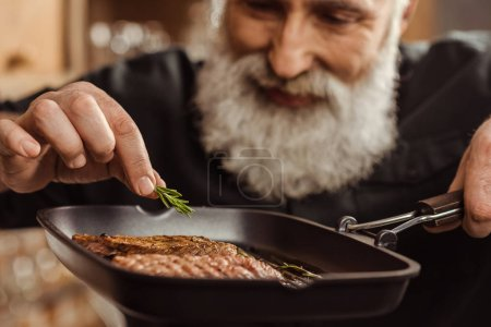 Photo for Close-up view of smiling bearded man putting rosemary on grilled steaks - Royalty Free Image